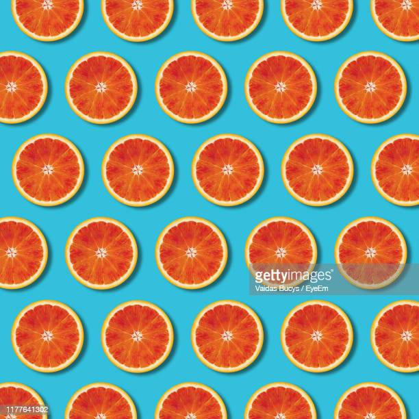 full frame shot of orange slices on blue background - halved stock pictures, royalty-free photos & images