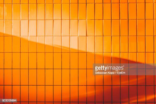 full frame shot of orange wall - orange farbe stock-fotos und bilder
