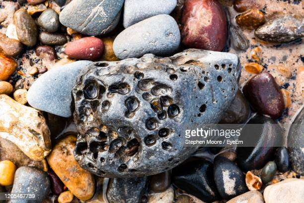 full frame shot of pebbles on rock - pebble stock pictures, royalty-free photos & images