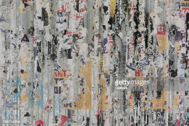 Full frame shot of peeling posters on weathered wall