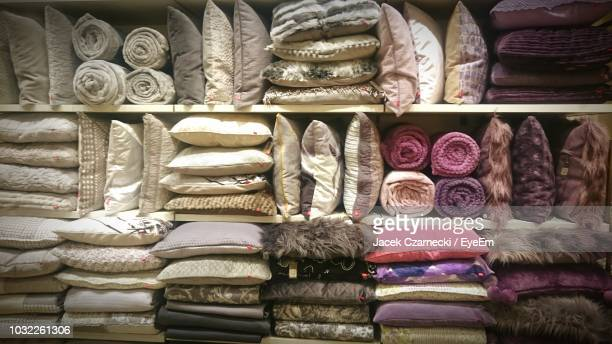 full frame shot of pillows with duvets arranged on shelves for sale in store - bedclothes stock pictures, royalty-free photos & images