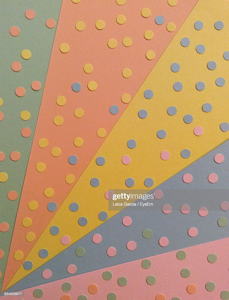 full frame shot of polka dots on multi colored paper stock photo