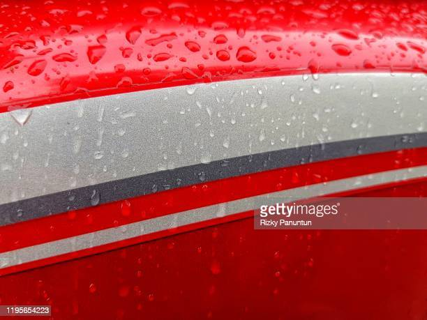 full frame shot of rain drops on motorcycle body - motorbike racing stock pictures, royalty-free photos & images