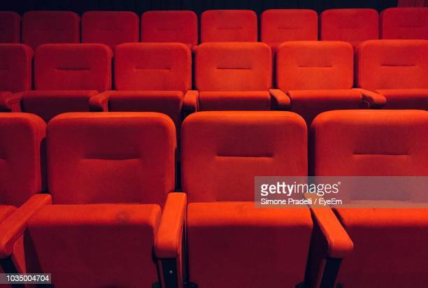 full frame shot of red empty seats in auditorium - absentie stockfoto's en -beelden