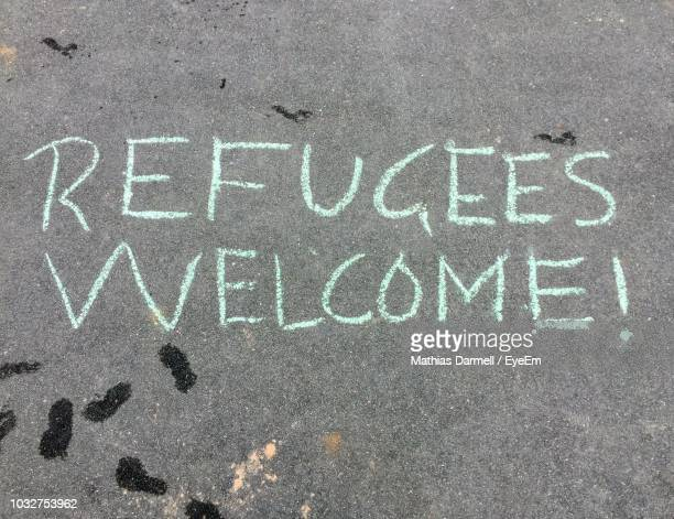 full frame shot of road with refugees welcome text - refugee stock pictures, royalty-free photos & images