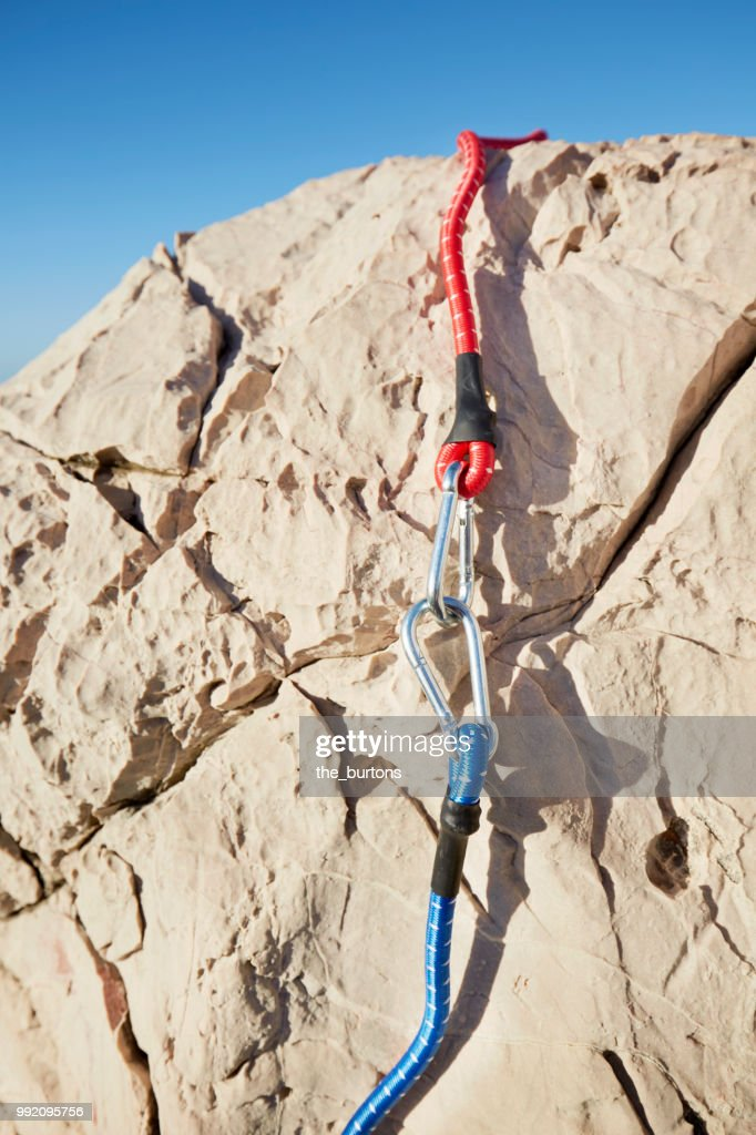 431140452f92 Full frame shot of rock with fissures and carabiner with two colored rope :  Stock Photo