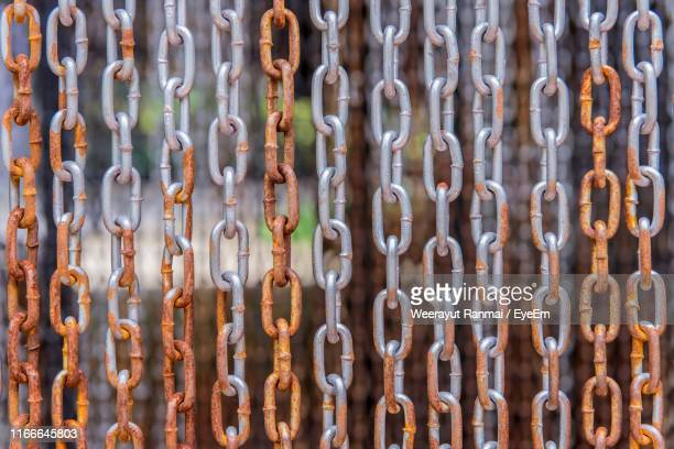 full frame shot of rusty chains hanging outdoors - chain stock pictures, royalty-free photos & images
