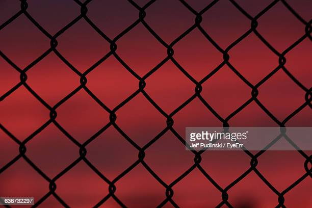 Full Frame Shot Of Silhouette Chainlink Fence Against Red Sky During Sunset