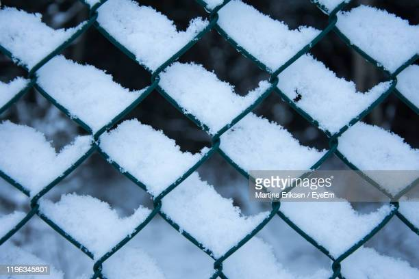 full frame shot of snow covered chainlink fence - eriksen stock pictures, royalty-free photos & images