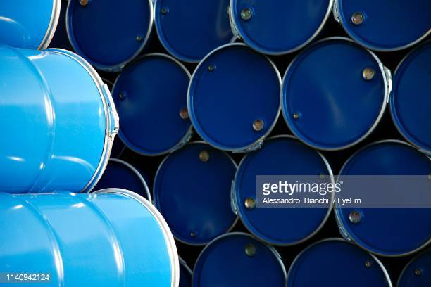full frame shot of stacked blue drums in warehouse - drum container stock photos and pictures