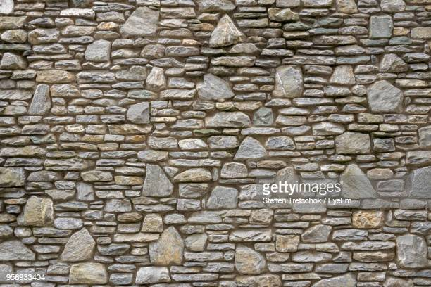 full frame shot of stone wall - stone material stock photos and pictures