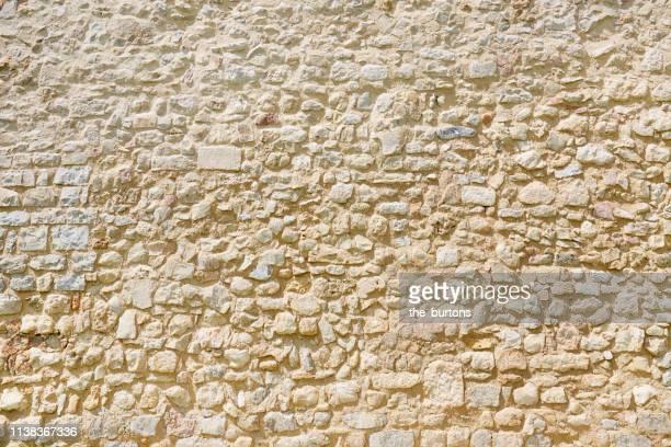 full frame shot of tall, old stone wall - stone wall stock-fotos und bilder