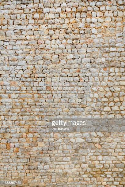 full frame shot of tall, old stone wall - stone wall texture stock pictures, royalty-free photos & images