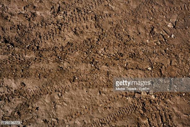 full frame shot of tire tracks on soil - erdreich stock-fotos und bilder