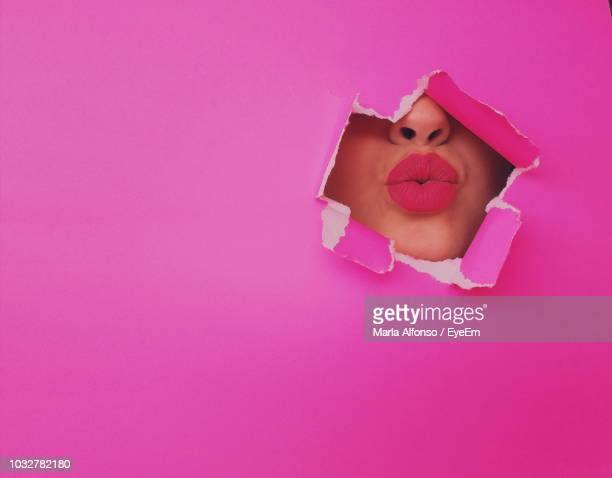 full frame shot of torn pink paper with woman puckering - puckering stock pictures, royalty-free photos & images