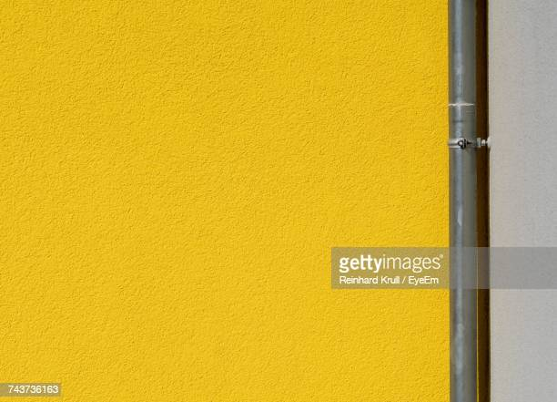 full frame shot of wall with pipe - yellow stock pictures, royalty-free photos & images