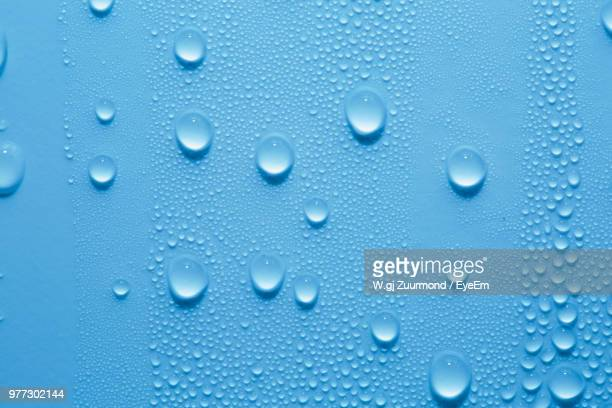 full frame shot of water drops on blue wall - regentropfen stock-fotos und bilder