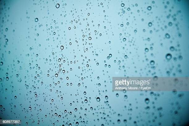 full frame shot of water drops on glass window during monsoon - vignettierung stock-fotos und bilder