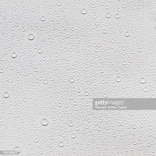 full frame shot of water drops on white table - wet stock pictures, royalty-free photos & images