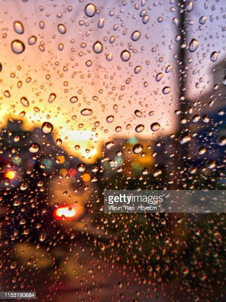 full frame shot of wet car window in rainy season during sunset - monsoon stock pictures, royalty-free photos & images