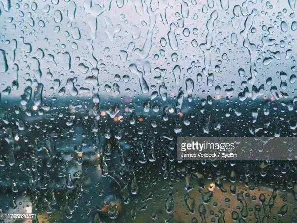 full frame shot of wet glass window in rainy season - torrential rain stock pictures, royalty-free photos & images