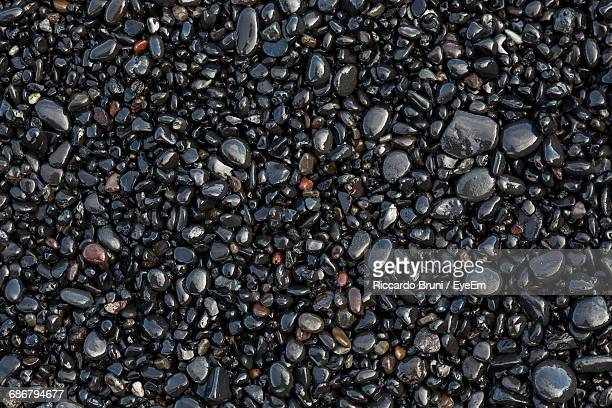 full frame shot of wet pebbles at beach - pebble stock photos and pictures