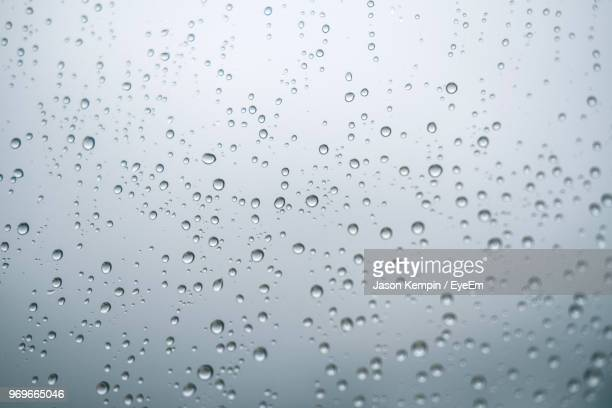 full frame shot of wet window during rainy season - regentropfen stock-fotos und bilder