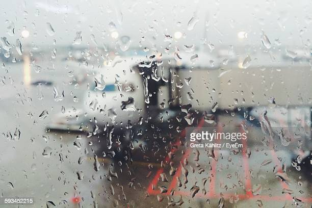 Full Frame Shot Of Wet Window Glass Against Airplane On Runway At Airport
