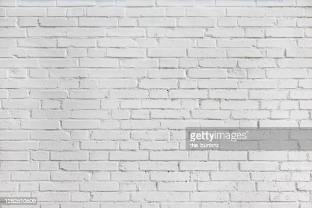 full frame shot of white painted brick wall, abstract background - ziegel stock-fotos und bilder