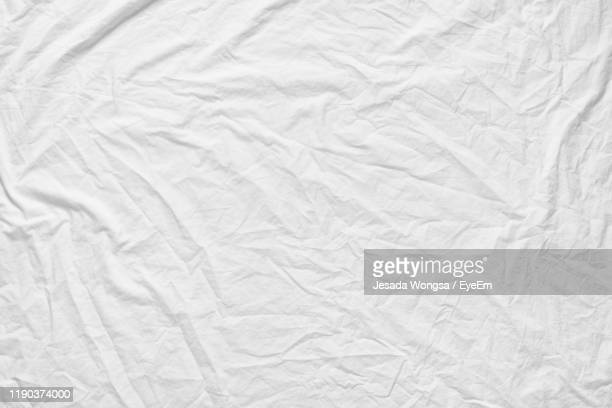 full frame shot of white sheet on bed - textile stock pictures, royalty-free photos & images