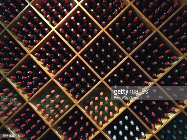 full frame shot of wine bottles in shelves - wine cork stock photos and pictures
