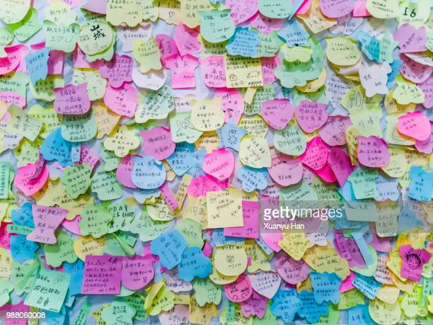 full frame shot of wishing notes on wall - bericht stockfoto's en -beelden