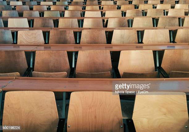 full frame shot of wooden chairs in auditorium - zuschauerraum stock-fotos und bilder