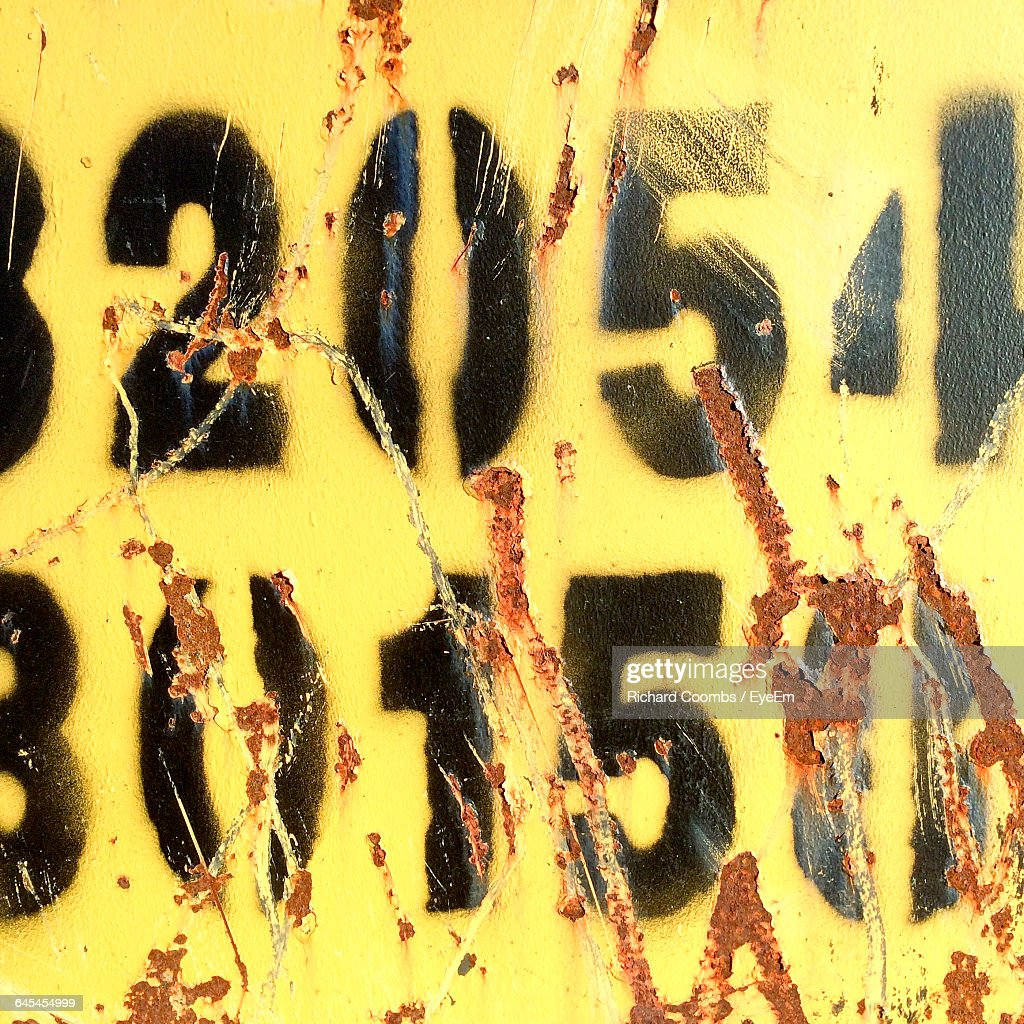 Full Frame Shot Of Yellow Weathered Wall With Numbers Stock Photo ...