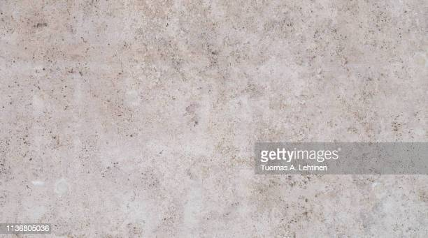 full frame texture background of a light brown stone slab. - stone wall stock-fotos und bilder