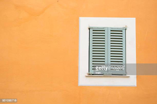 Full frame texture, Closed white Window Of House On Saturated Yellow Wall