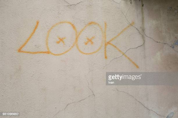 Full frame texture, graffiti on old cement wall with the letters LOOK