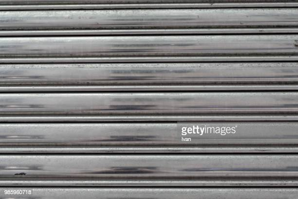 full frame texture, rusty iron shutter textured roll-up door - industrial door stock pictures, royalty-free photos & images