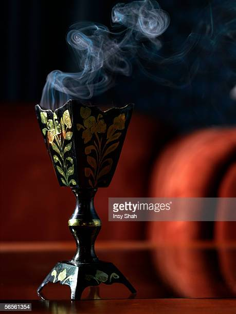 Full frame view of incense burner standing on the glass table.