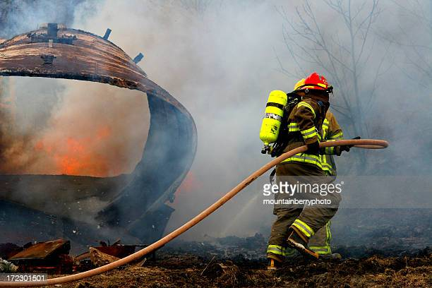 full geared firefighter with water hose on field - wildfire stock photos and pictures