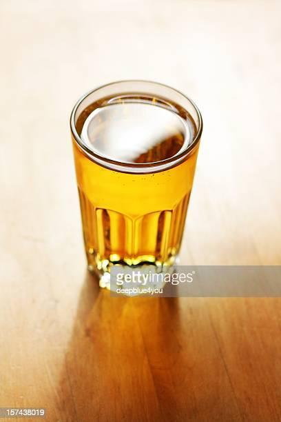 Full glass of apple juice in sunlight