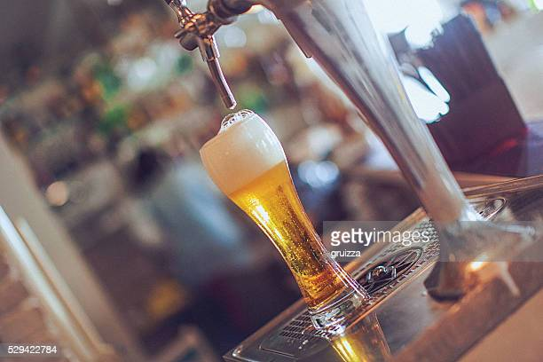 Full glass of beer under the faucet at bar