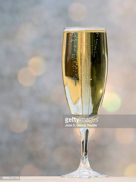 Full glass of champagne illuminated by sunlight and a colorful background