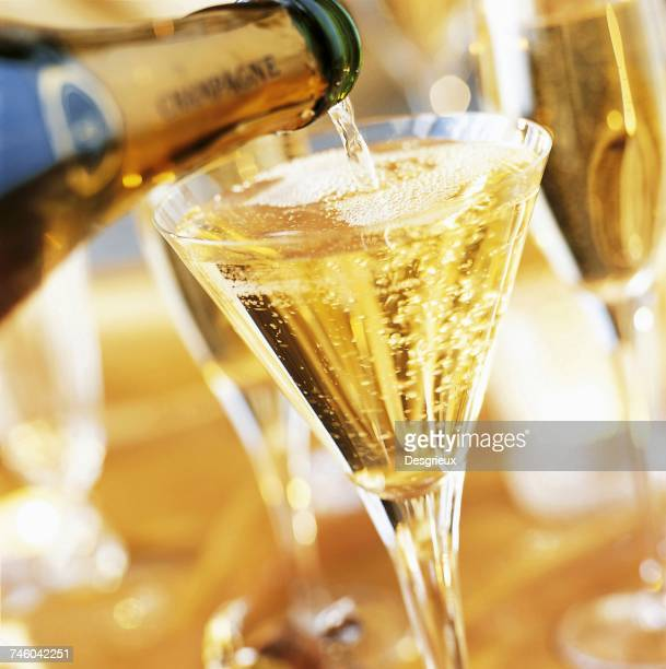 full glass of champagne with pouring champagne bottle - champagne colored stock pictures, royalty-free photos & images