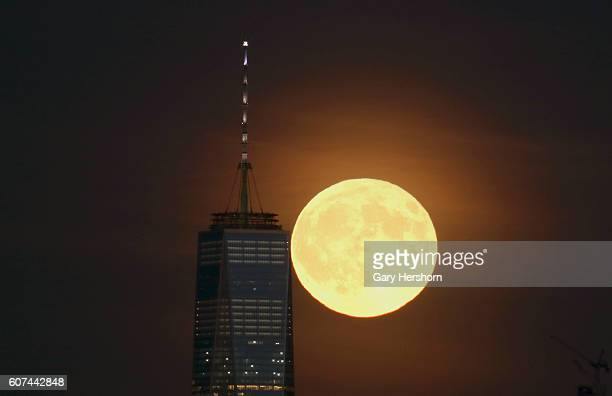 A full harvest moon rises behind Lower Manhattan and One World Trade Center in New York City on September 16 2016 as seen from Newark NJ