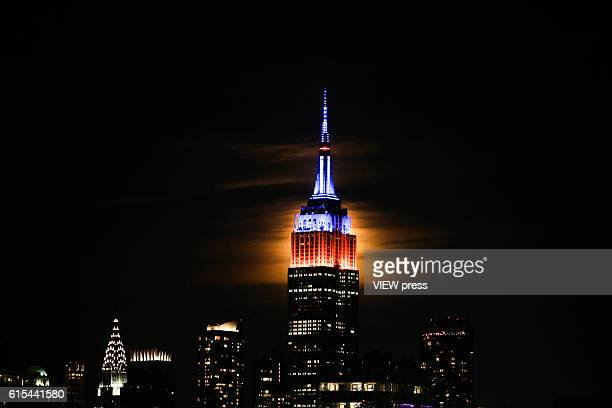 A full Hunter's super moon rises behind middle Manhattan and Empire State Building in New York City on October 16 2016 as seen from Hoboken NJ