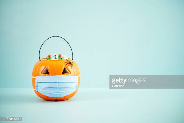full jack o'lantern trick or treat bucket with face mask halloween background - illness prevention stock pictures, royalty-free photos & images