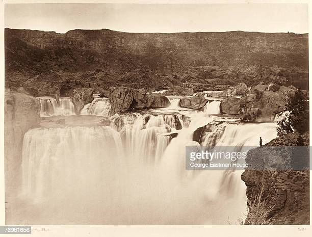 Full lateral view of the upper level of Shoshone Falls on the Snake River with one person standing next to it at right for scale, Idaho, 1874.