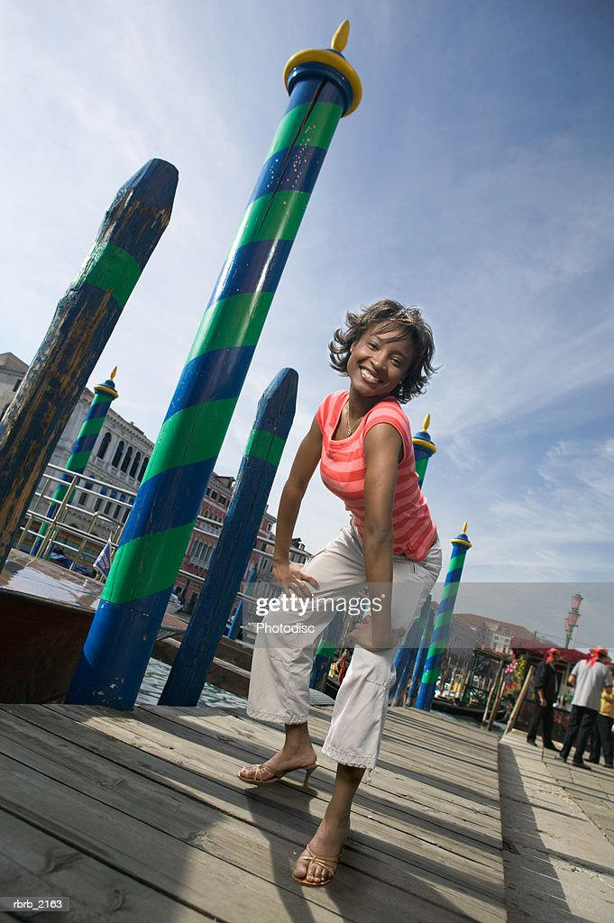 full legth wide shot of a young adult woman as she playfully poses on a dock : Stockfoto