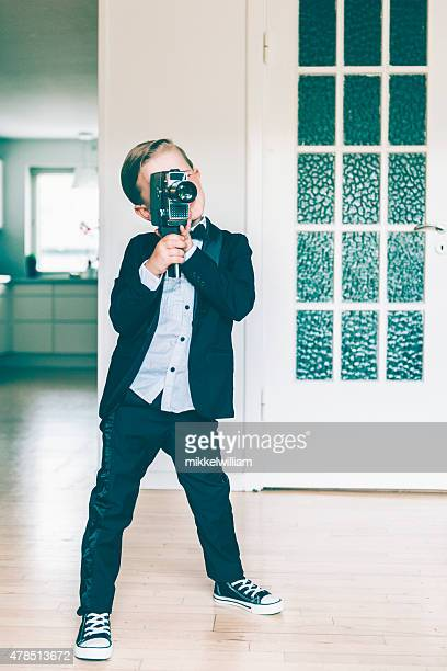 Full lenght portrait of boy shooting video with retro camera